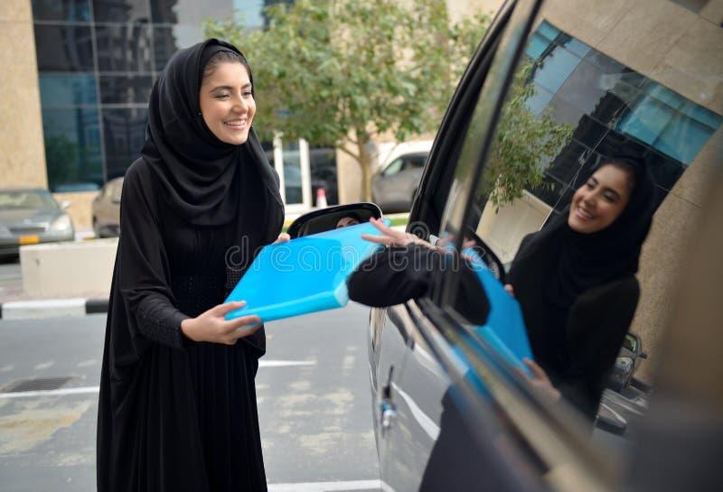Donne arabe di affari di Emarati che entrano nell'automobile immagine stock libera da diritti