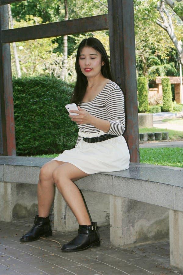 Donne asiatiche che giocano telefono nel parco immagini stock