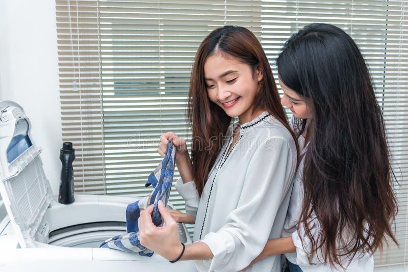 Donne asiatiche delle coppie che fanno insieme lavoro domestico ed i lavoretti davanti alla lavatrice e che caricano i vestiti ne fotografie stock