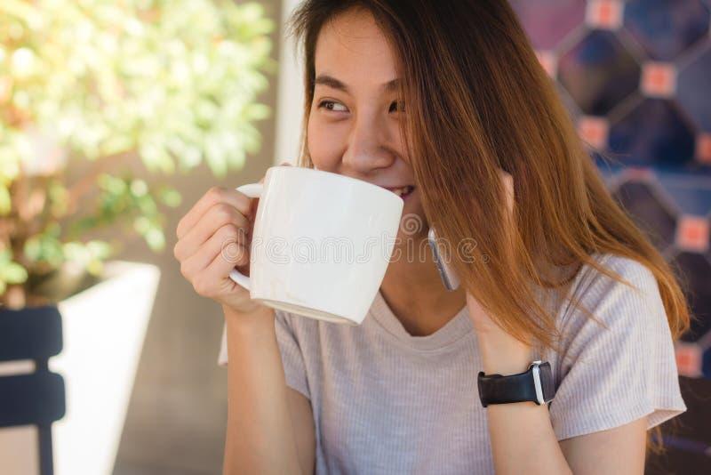 Donne asiatiche di affari di sorriso felice che utilizzano telefono cellulare di conversazione che si siede nel caffè fotografia stock