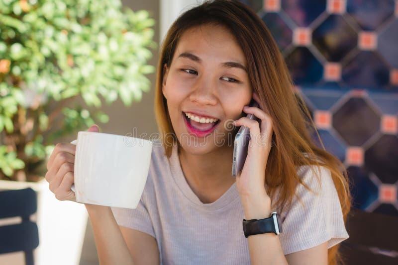 Donne asiatiche di affari di sorriso felice che utilizzano telefono cellulare di conversazione che si siede nel caffè e che tiene fotografia stock
