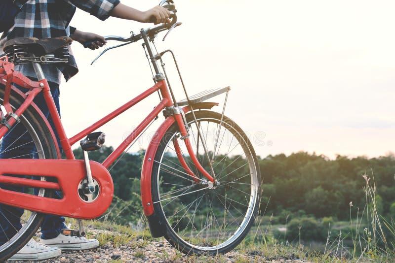 Donne asiatiche felici dei pantaloni a vita bassa con la bicicletta sulla strada fotografia stock