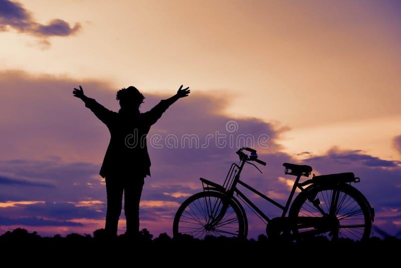 Donne asiatiche felici dei pantaloni a vita bassa della siluetta con la bicicletta immagini stock libere da diritti