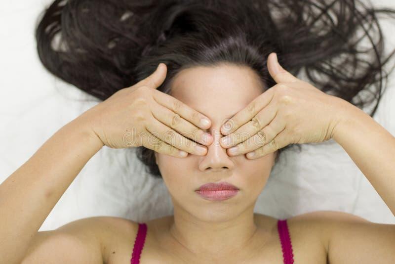 Donne asiatiche lunatiche che si trovano sulla terra con capelli lunghi neri turbato sostituto e mostrare vicino i suoi occhi immagini stock