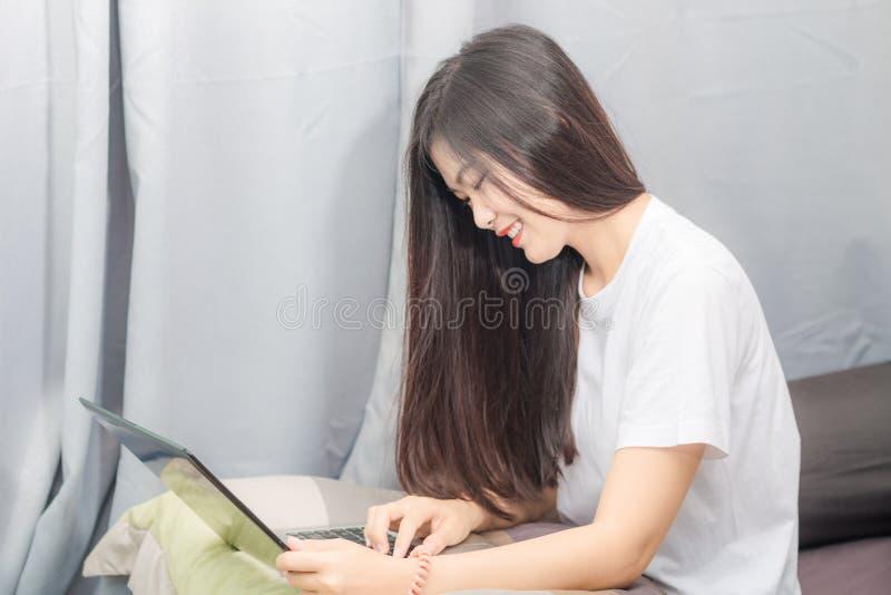 Donne asiatiche sorridenti felici che passano in rassegna Internet sul computer portatile fotografia stock