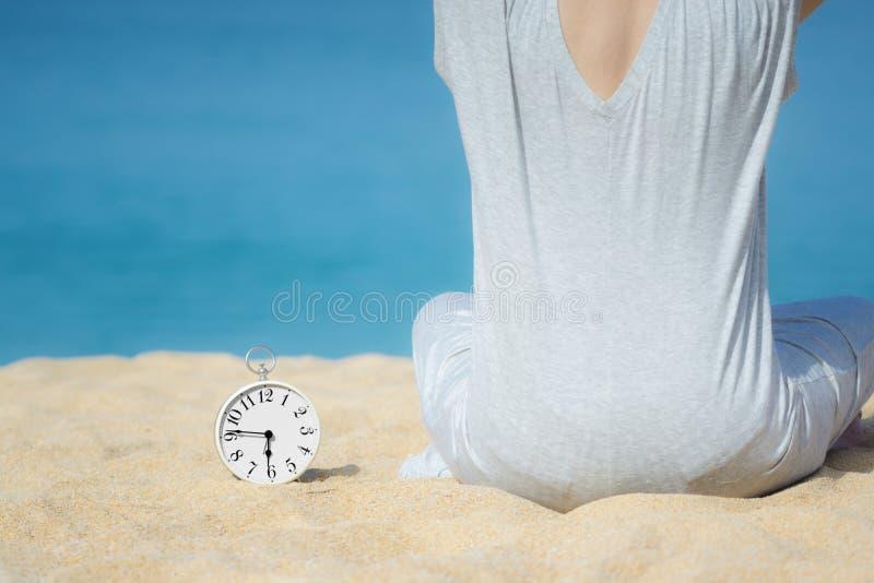 Donne asiatiche in un vestito grigio che si siede accanto alla sveglia bianca disposta sulla sabbia Mare e cielo blu come fondo C fotografie stock libere da diritti