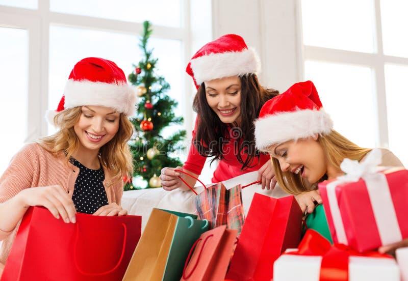 Donne in cappelli dell'assistente di Santa con i sacchetti della spesa fotografia stock