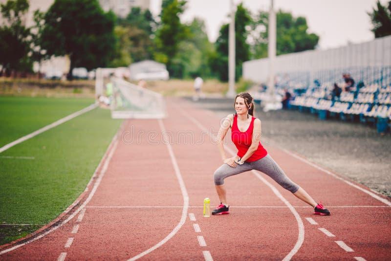 Donne caucasiche di forma fisica di sport che fanno riscaldamento prima dell'esercizio Atleta che allunga le gambe che fanno risc fotografia stock libera da diritti