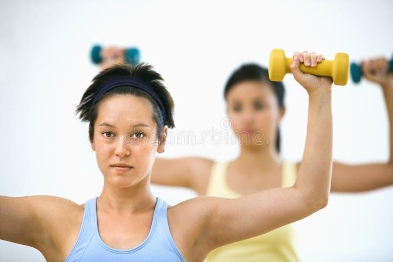 Donne che alzano i pesi della mano immagine stock