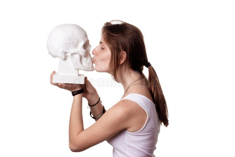 Donne che baciano un cranio umano di gesso isolare fotografie stock libere da diritti