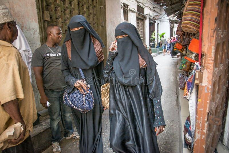 Donne che camminano attraverso la città di pietra, Zanzibar tanzania fotografie stock
