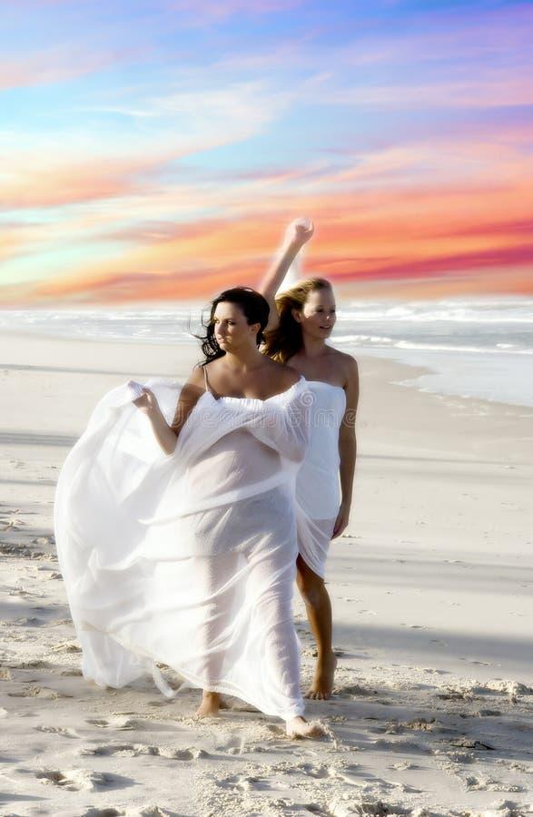 Donne che camminano lungo la spiaggia immagine stock