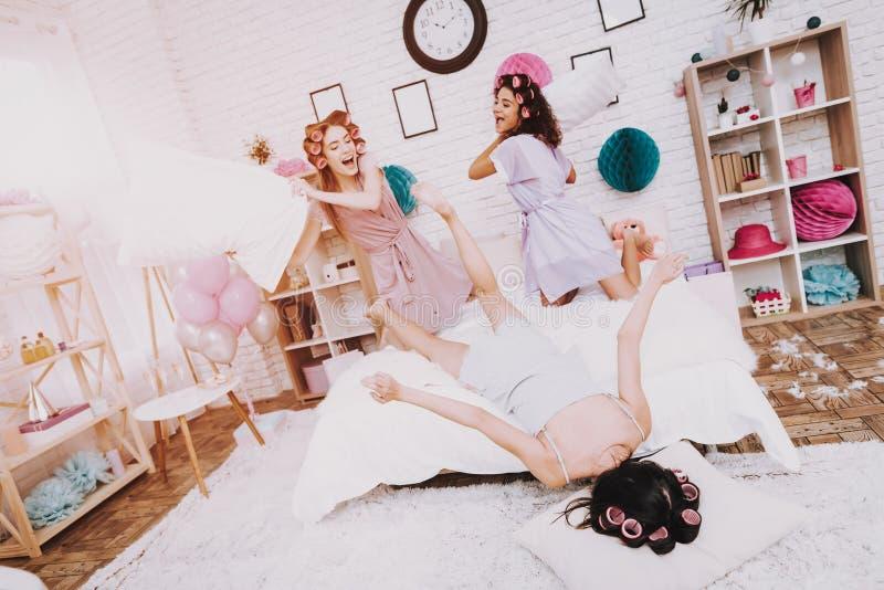Donne che combattono con i cuscini sull'interno bianco fotografia stock libera da diritti