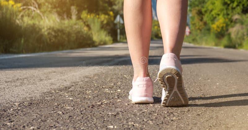 Donne che eseguono i piedi sulla via nel parco, stile di sport di vita sano, pareggiante eseguendo concetto di esercizio, insegna immagini stock libere da diritti