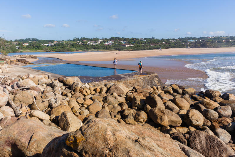 Donne che esplorano lo stagno di marea della spiaggia immagini stock libere da diritti