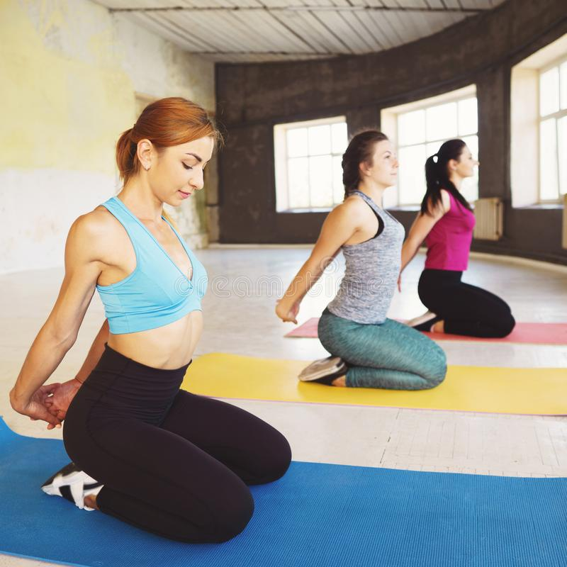 Donne che fanno allungando gli esercizi durante la classe di yoga immagine stock libera da diritti