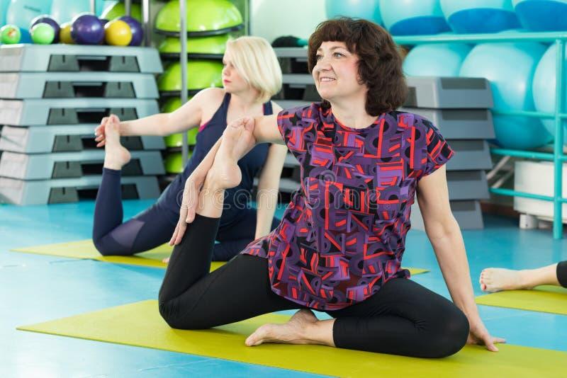 Donne che fanno esercizio di yoga nella palestra fotografia stock libera da diritti