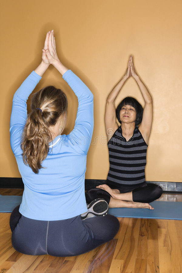 Donne che fanno yoga alla ginnastica. immagine stock