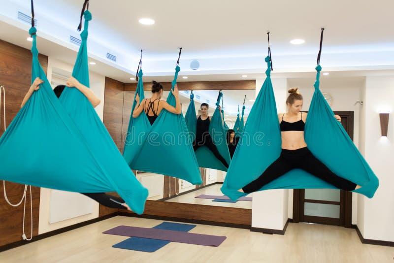 Donne che fanno yoga della mosca che allunga gli esercizi in amaca Stile di vita di benessere e di misura immagine stock
