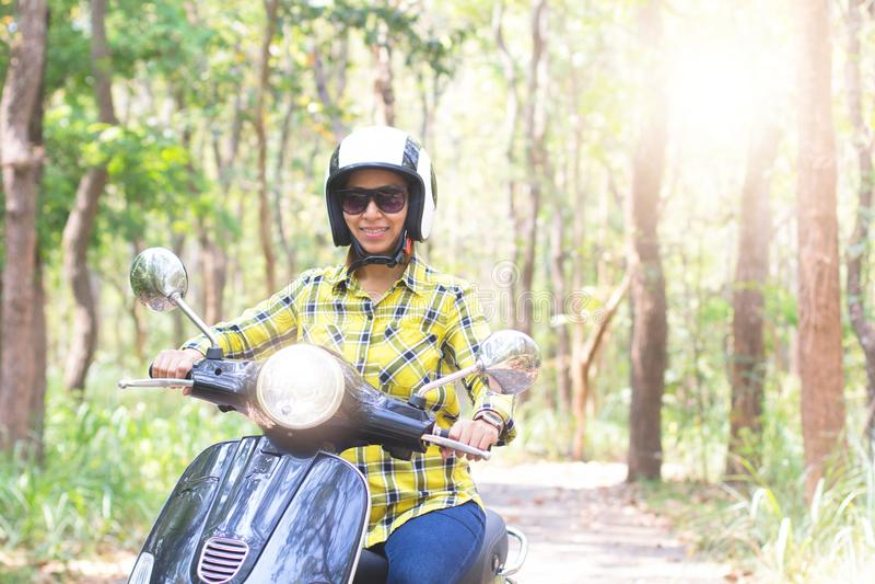 Donne che guidano il loro motorino attraverso la foresta fotografie stock