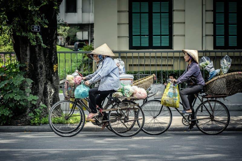 Donne che guidano le biciclette sulla via a Hanoi fotografia stock