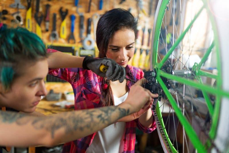 Donne che lavorano in un'officina riparazioni della bicicletta fotografie stock libere da diritti