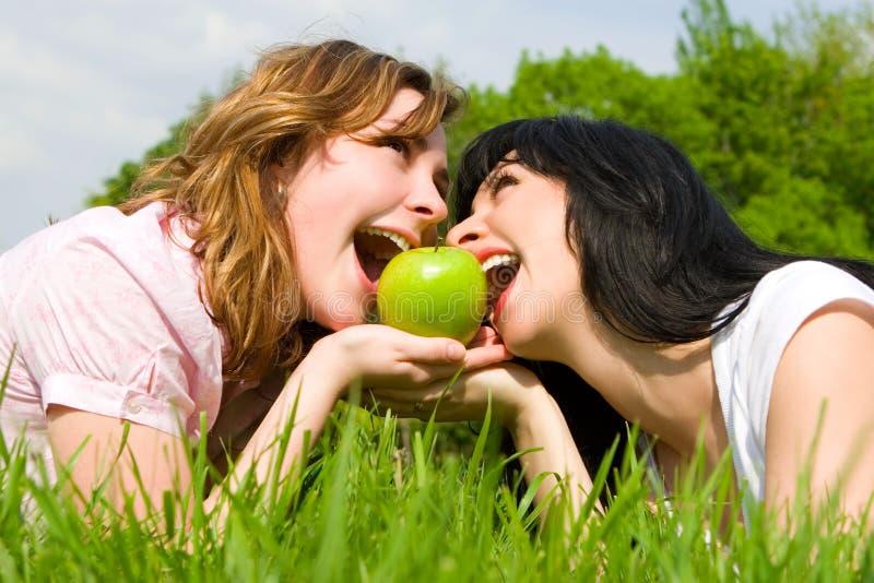 Donne che mangiano mela sul glade di estate fotografie stock libere da diritti