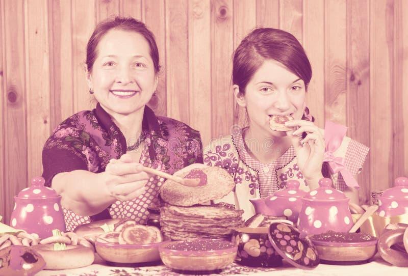 Donne che mangiano pancake con il caviale durante lo Shrovetide fotografia stock