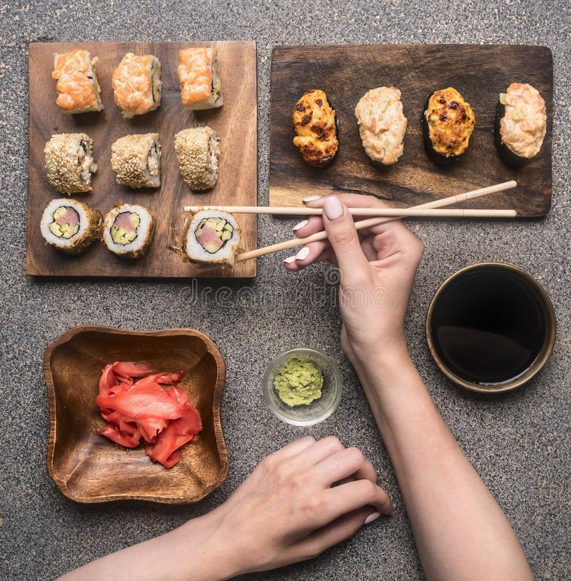 Donne che mani del ` s prende i sushi con i bastoncini, zenzero, wasabi, salsa di soia, vari rotoli sono presentati su un fondo r fotografia stock