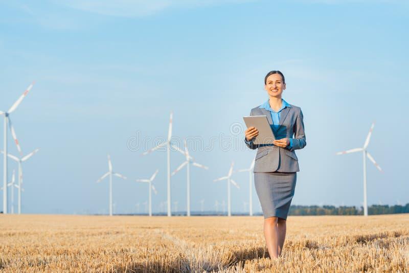 Donne che mettono soldi in un investimento etico dei generatori eolici fotografie stock
