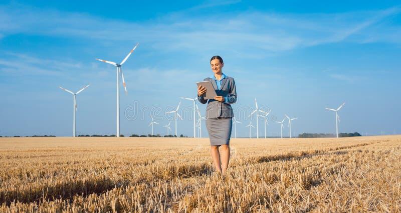 Donne che mettono soldi in un investimento etico dei generatori eolici immagini stock libere da diritti