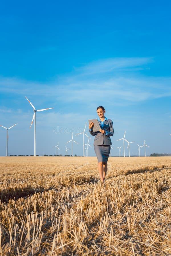 Donne che mettono soldi in un investimento etico dei generatori eolici fotografia stock libera da diritti