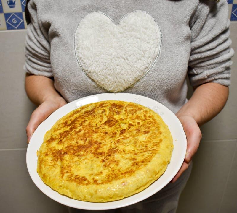 donne che mostrano su un piatto bianco un'omelette spagnola cucinata con le uova e le patate La donna porta una camicia con un gr fotografie stock