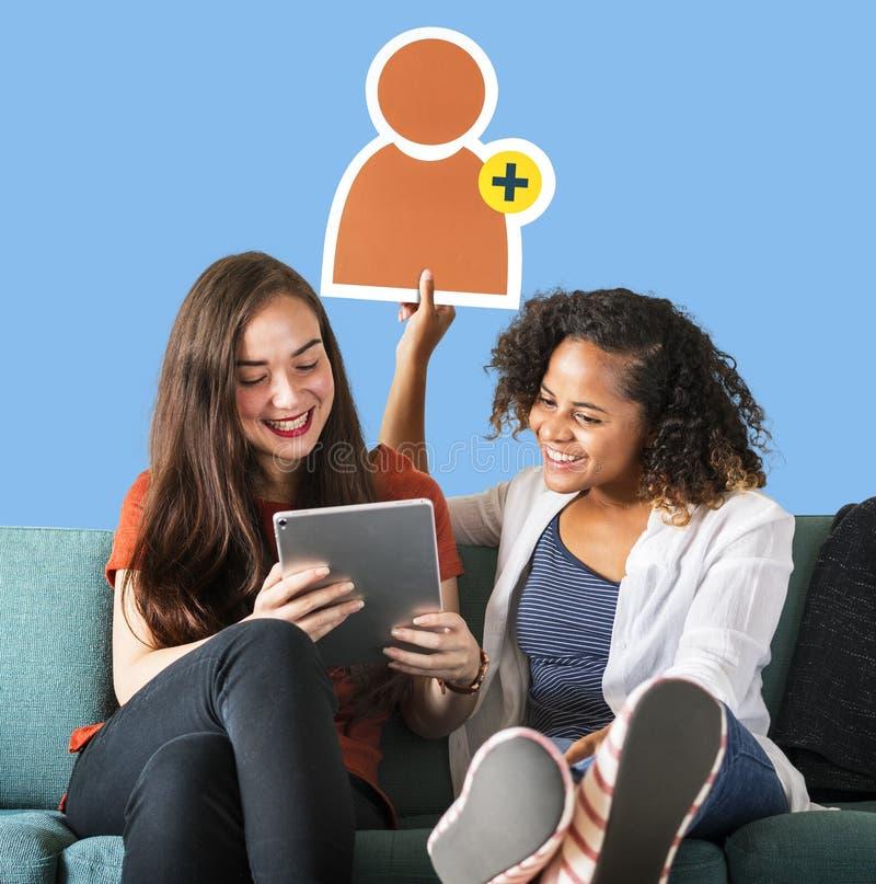 Donne che mostrano un'icona di richiesta dell'amico e che per mezzo di una compressa fotografie stock libere da diritti