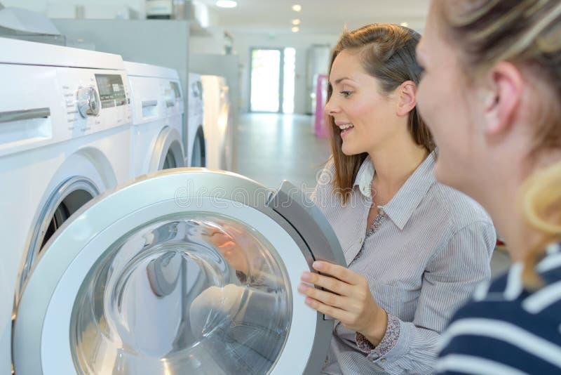 Donne che osservano le lavatrici in deposito immagini stock libere da diritti
