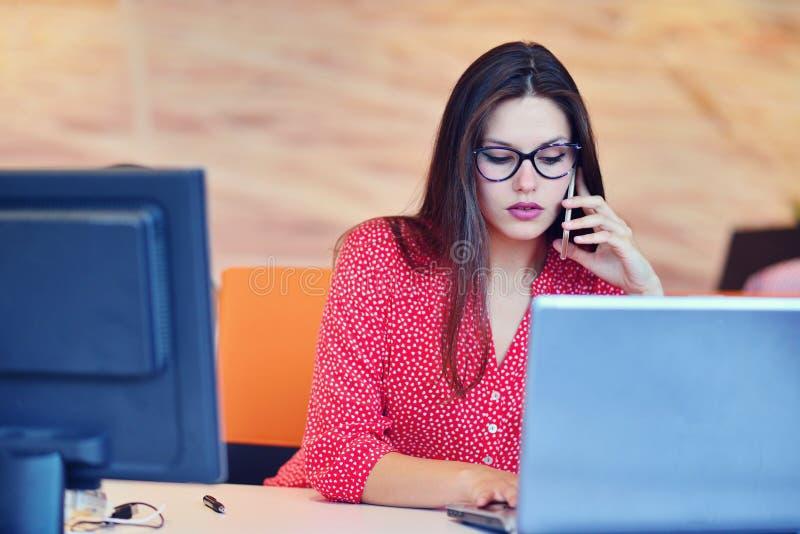 Donne che parlano sul telefono Riuscita donna di affari che lavora all'ufficio immagine stock