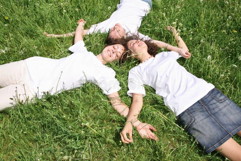 Donne che pongono su un'erba immagini stock