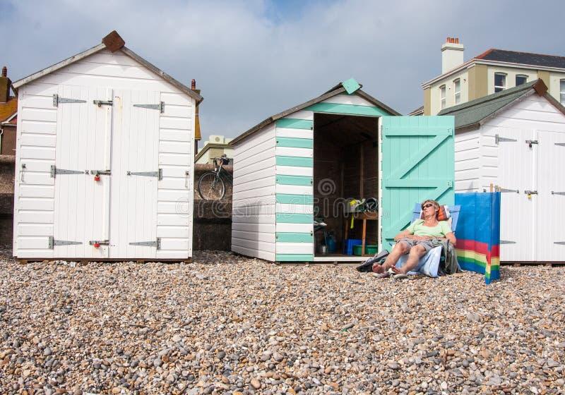 Donne che prendono il sole fuori della capanna della spiaggia fotografie stock libere da diritti