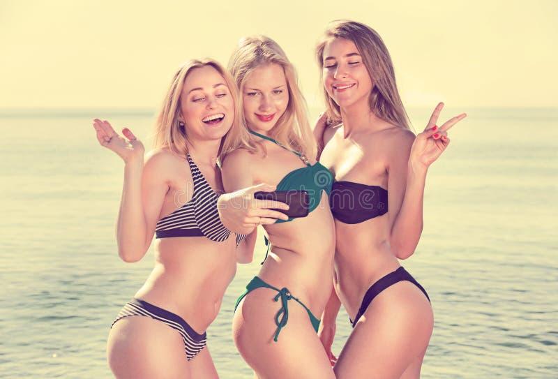Donne che prendono la foto di auto sulla spiaggia fotografia stock