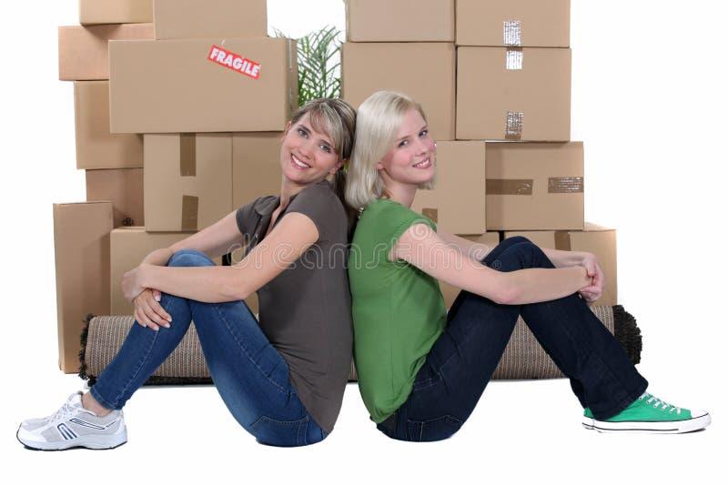Donne che si siedono dalle scatole fotografie stock