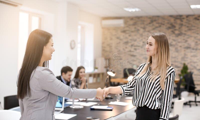 Donne che stringono le mani in ufficio Riuscita riunione d'affari immagine stock libera da diritti