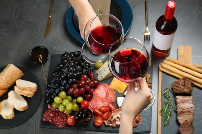 Donne che tengono i vetri di vino rosso sopra la tavola con gli spuntini fotografia stock libera da diritti