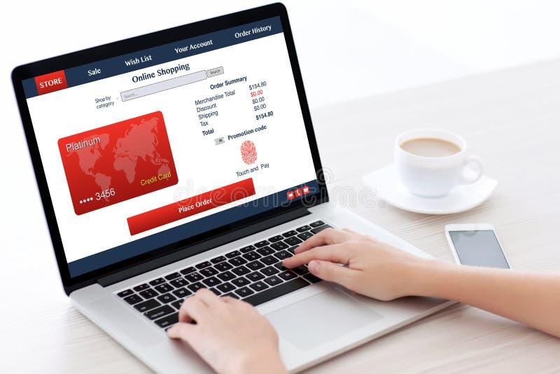 Donne che tengono l'impronta digitale del computer portatile e la carta di credito shoping online immagini stock
