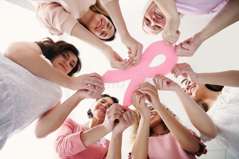 Donne che tengono nastro di carta rosa, vista dal basso fotografia stock