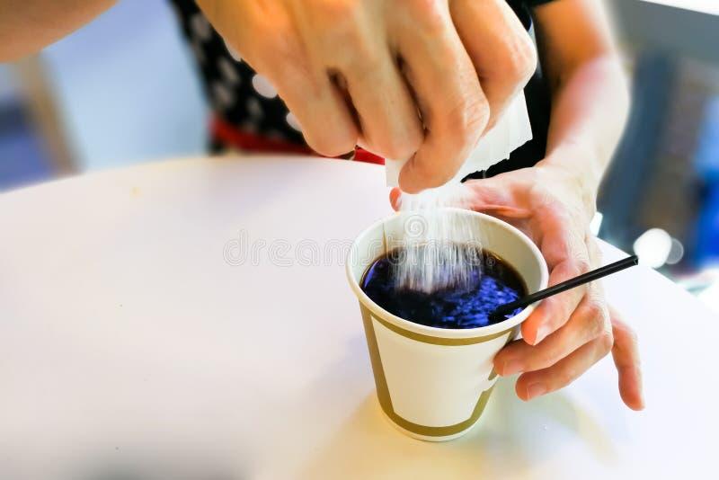 Donne che versano i granelli dello zucchero dalla bustina nel caffè nero fotografie stock libere da diritti