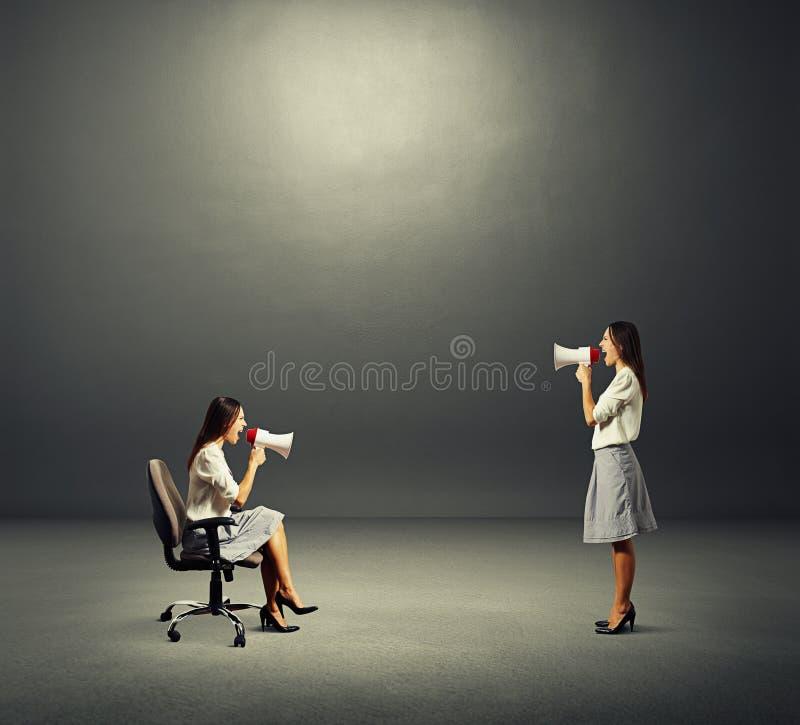 Donne con il megafono sopra buio fotografie stock