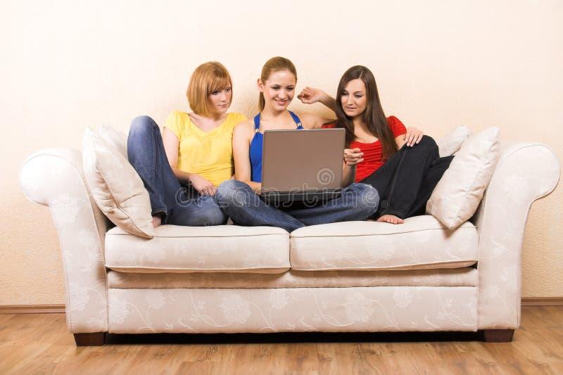 Donne con un computer portatile su un sofà fotografia stock libera da diritti