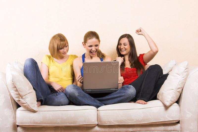 Donne con un computer portatile su un sofà fotografie stock libere da diritti