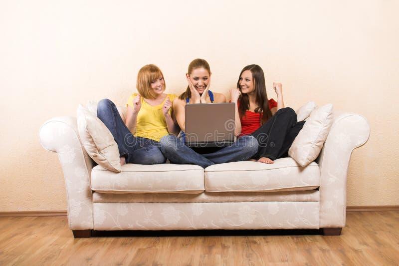 Donne con un computer portatile su un sofà fotografie stock