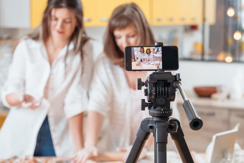 Donne culinarie del vlog che cuociono hobby online dello smartphone fotografia stock